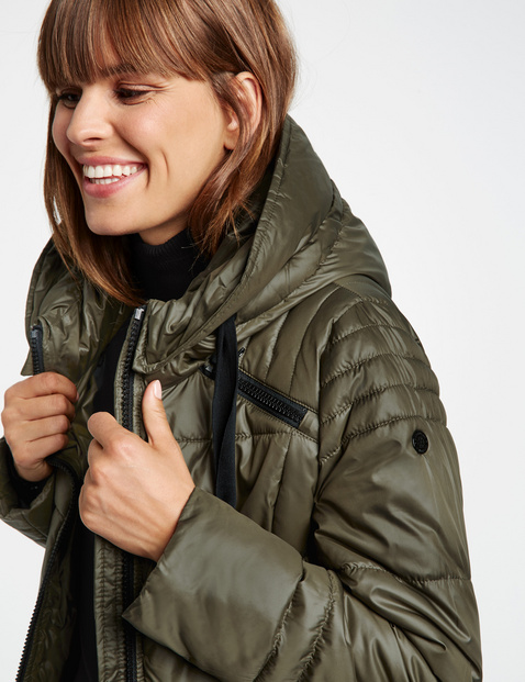 Błyszczący pikowany płaszcz z detalami w postaci zamków