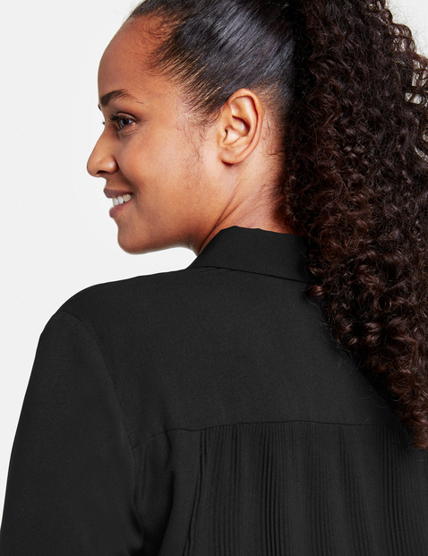 Long, flared blouse with pleats on the back