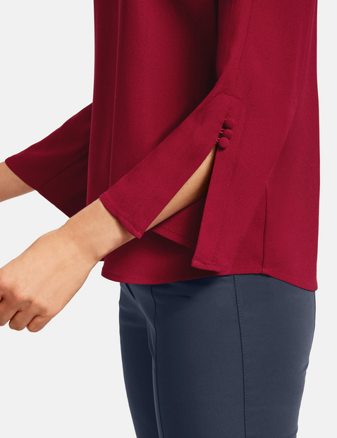 Blouse with sleeve slits