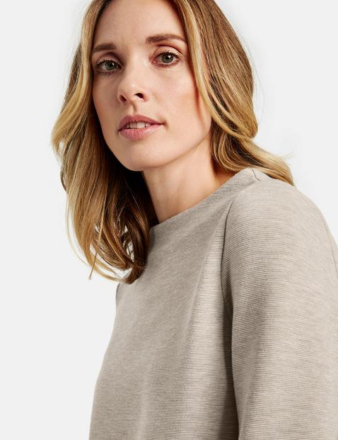 Long sleeve top with an asymmetric hem